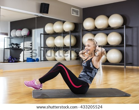 Woman Doing Crunches On Exercise Mat In Gym