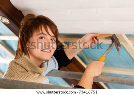 Woman doing dry walling, working under a roof slope - stock photo