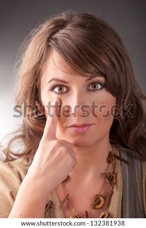 Woman doing EFT on the under eye point. Emotional Freedom Techniques, tapping, a form of counseling intervention that draws on various theories of alternative medicine. - stock photo