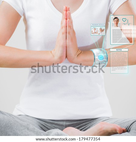 Woman doing exercise wearing smart wearable device with futuristic interface - stock photo