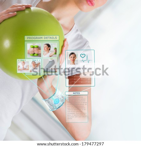 Woman doing exercise with ball wearing smart wearable device with futuristic interface