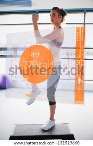 Woman doing exercise with futuristic interface showing calories lost - stock photo