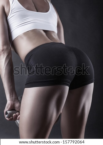 Woman doing exercises with dumbbell squats on a dark background - stock photo