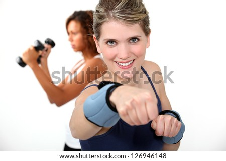 woman doing exercises with wrist weights - stock photo