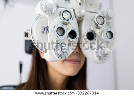 Woman doing eyesight measurement with optical phoropter - stock photo