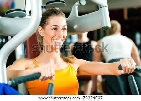 Woman doing fitness training on a butterfly machine with weights in gym or fitness club