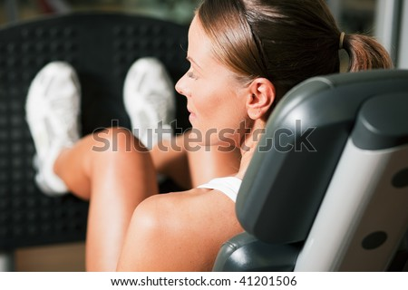Woman doing fitness training on a leg extension push machine with weights in a gym - stock photo