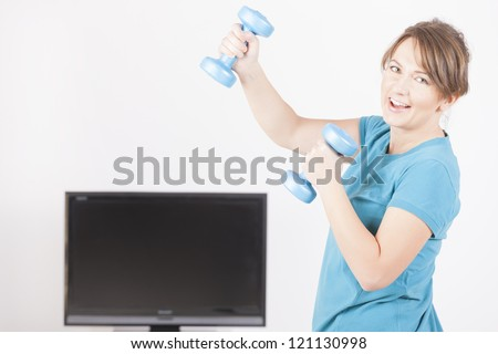 Woman doing fitness with dumb-bells at home using on screen TV instructions - stock photo