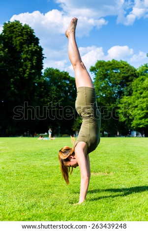 Woman doing handstand in park - stock photo