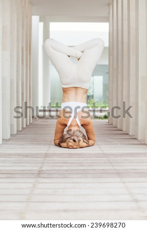 woman doing headstand asana in a spacious studio - stock photo