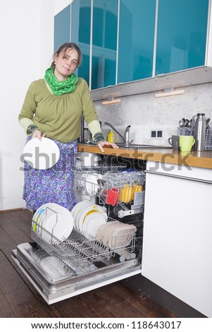 woman doing housework and putting dishes in the dishwasher.