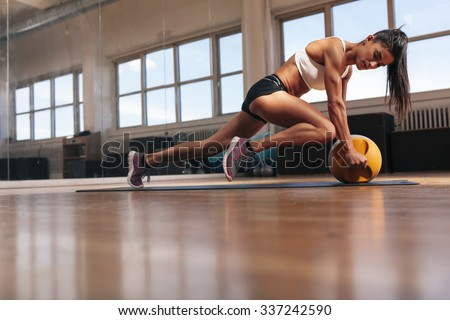 Woman doing intense core exercise on fitness mat. Muscular young woman doing workout at gym. - stock photo