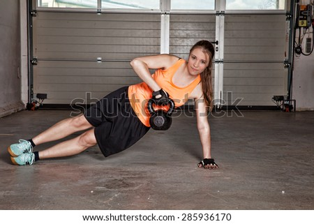 woman doing kettlebells pull up - stock photo