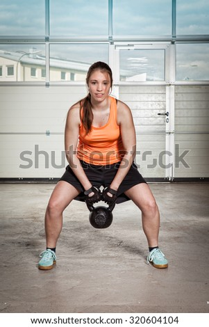 woman doing kettlebells pull up