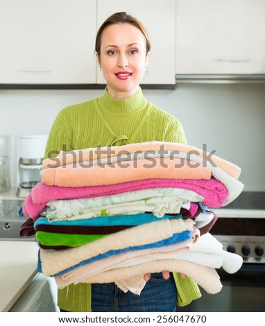 Woman doing laundry indoors. She is standing near washing machine and holding a heap of clean towels in her hands - stock photo