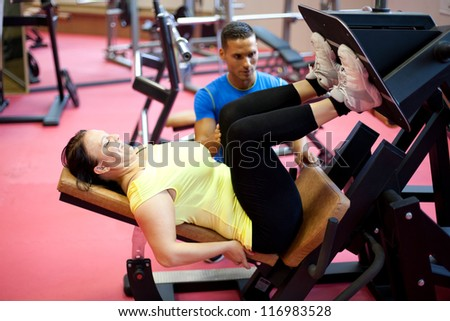 Woman doing leg exercise under personal trainer's supervision. At the gym.