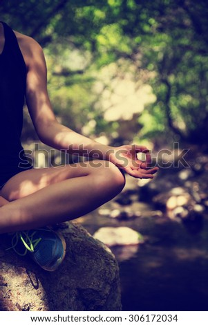 woman doing lotus pose on rock on mountain creek with retro instagram filter with shallow depth of field - stock photo