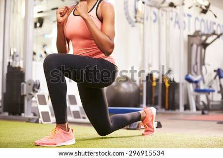 Woman doing lunges in a gym, crop - stock photo
