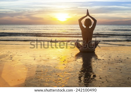 Woman doing meditation near the ocean. Yoga silhouette. - stock photo