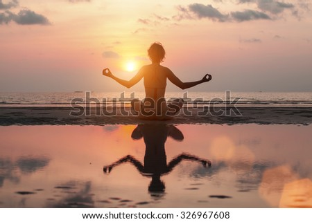 Woman doing meditation on the Sea beach. Yoga silhouette. - stock photo