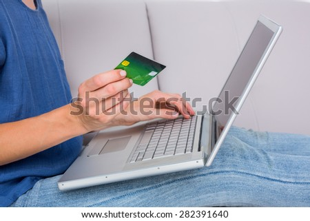 Woman doing online shopping with laptop and credit card on the couch - stock photo