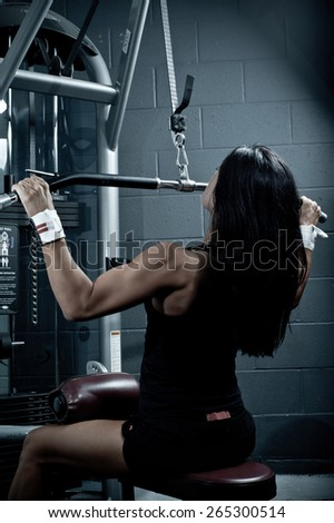 Woman doing pull-ups on a machine in the gym - exercising lifting dumbbells
