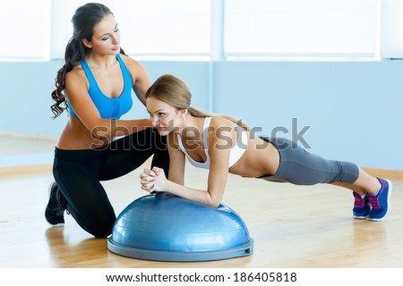 Woman doing push-ups. Beautiful young woman in sports clothing doing push-up with her personal instructor - stock photo