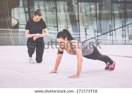 Woman doing push-ups exercises with her personal trainer in a modern urban context. She is wearing gray and black sportswear and a phone holder, the trainer look at watch and incite her - stock photo