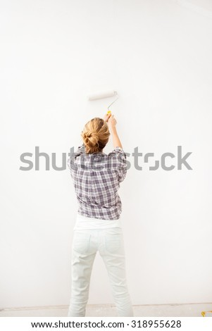 Woman doing repairs. Female paints the wallpaper roll - stock photo