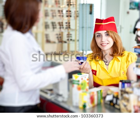 woman doing shopping in supermarket and paying by credit card