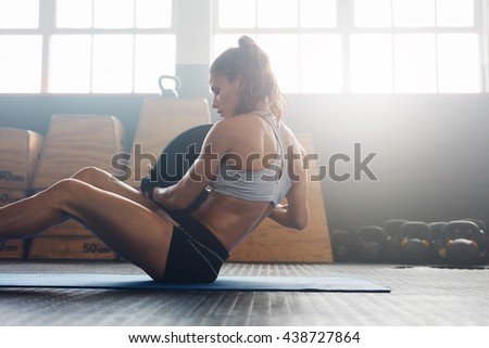 Woman doing sit ups with holding a weight plate. Fitness woman working out on core muscles at cross fit gym. - stock photo