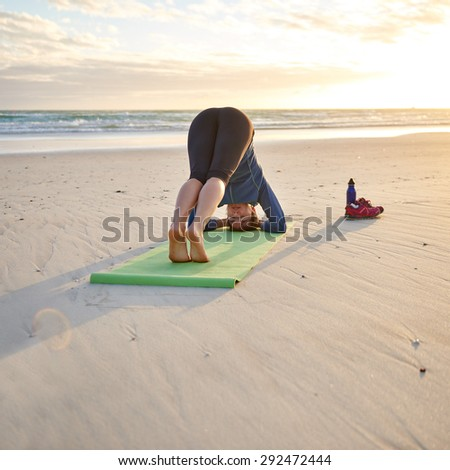 Woman doing some early morning yoga on her yoga-mat at the beach - stock photo