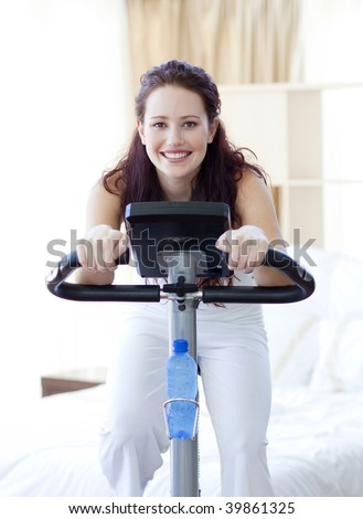 Woman doing spinning bike in her bedroom at home