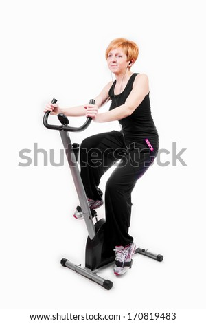 Woman doing sports on exercise bike