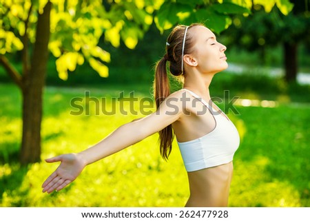 Woman doing sports outdoors.  Young beautiful healthy woman smiling and doing relaxing yoga in the green sunny park. Sports lifestyle and recreation concept.  - stock photo