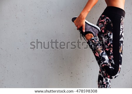 Woman doing stretching exercises for legs. Sports background.