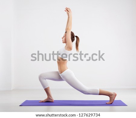 Woman doing stretching exercises in a gym - stock photo