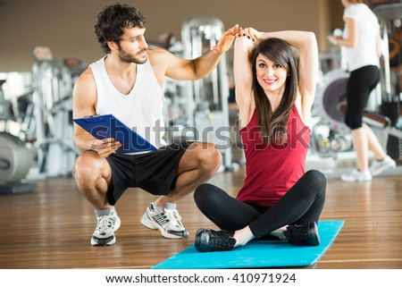Woman doing stretching in a gym while a personal trainer watches her - stock photo
