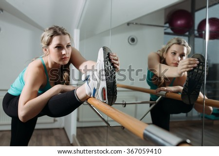 Woman doing stretching near barre in fitness center