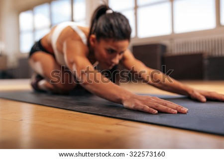 Woman doing stretching workout on fitness mat, focus on hands, fitness female performing yoga on exercise mat at gym. - stock photo