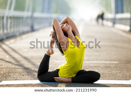 Woman doing stretching yoga exercises outdoors on the bridge - stock photo