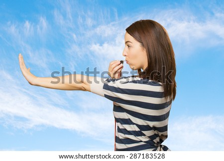 Woman doing the stop gesture and using a whistle. Over clouds background - stock photo
