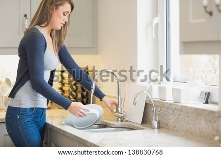 Woman doing the washing up in kitchen - stock photo
