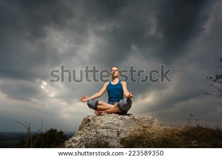 Woman doing yoga against the setting sun. Fitness classes outdoors. Stormy sky with sunshine. Attractive fitness woman, lifestyle portrait, caucasian model - stock photo