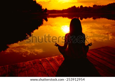 Woman doing yoga at sunset - stock photo