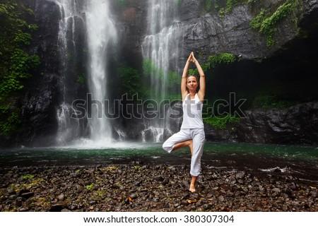 woman doing yoga between waterfalls on Bali - stock photo