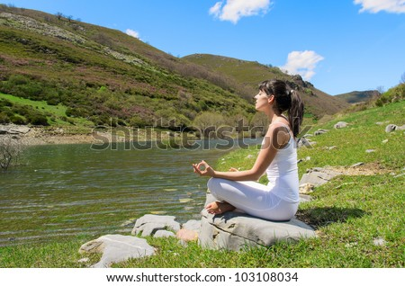 Woman doing yoga breathing exercises on nature. Caucasian young woman in white relaxing near a mountain river. - stock photo
