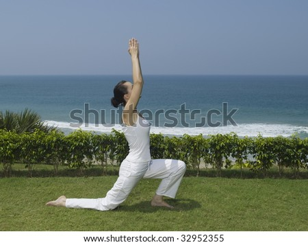 woman doing yoga exercise by the seaside - stock photo