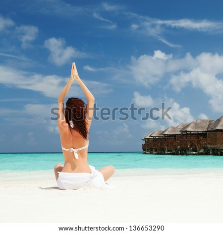 woman doing yoga exercises on the beach - stock photo