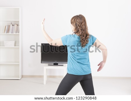 Woman doing yoga exerise at home using on screen TV instructions - stock photo